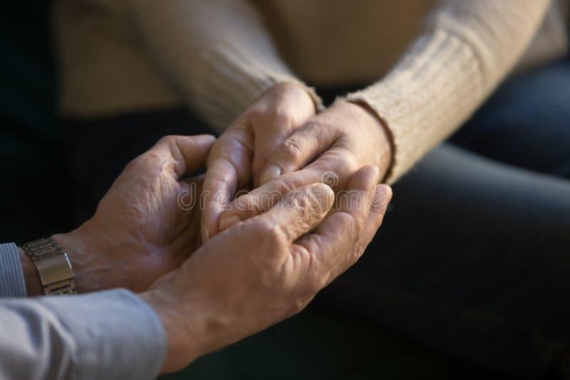 Конец вверх постарел пары держа руки, показывающ поддержку и любовь стоковые изображения rf