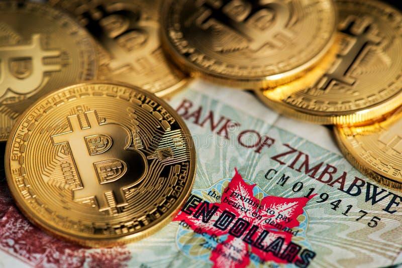 Конец вверх по взгляду банкноты гиперинфляции Зимбабве и монеток Bitcoin стоковое фото rf