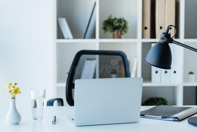 конец вверх по взгляду рабочего места с цветками доской сзажимом для бумаги и стеклом ноутбука воды в современном стоковое изображение rf