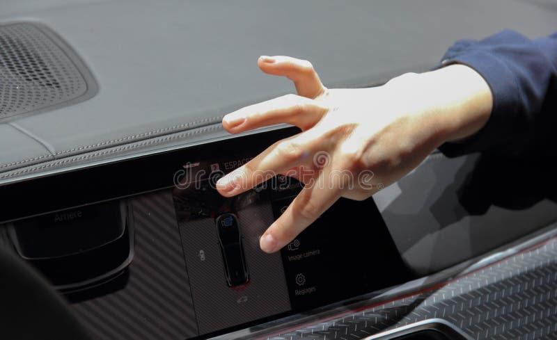 Конец вверх по взгляду руки женщины на экране касания приборной панели автомобиля стоковое фото rf