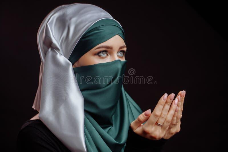 Конец вверх по взгляду со стороны снятому мусульманской молодой женщины в зеленом hijab молит бога стоковое фото rf