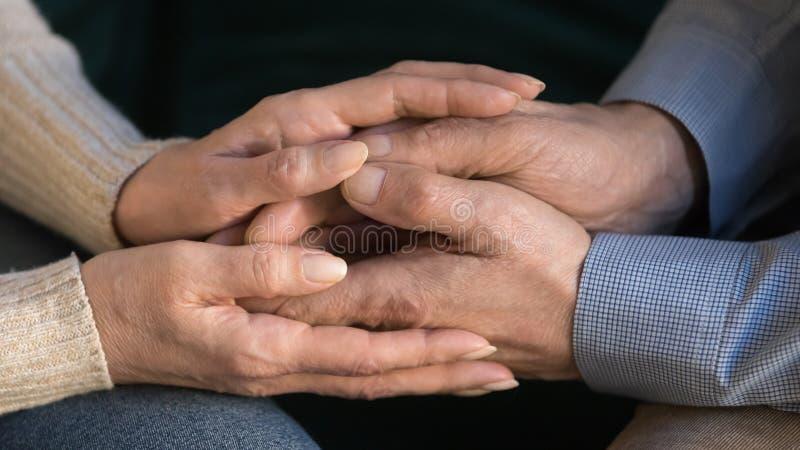 Конец вверх по достигшим возраста рукам супруга удерживания жены, показывая поддержку, любовь стоковые фотографии rf