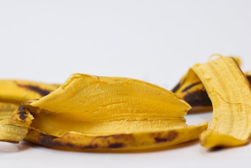 Конец вверх по желтой корке банана изолированной на белой предпосылке стоковые фотографии rf