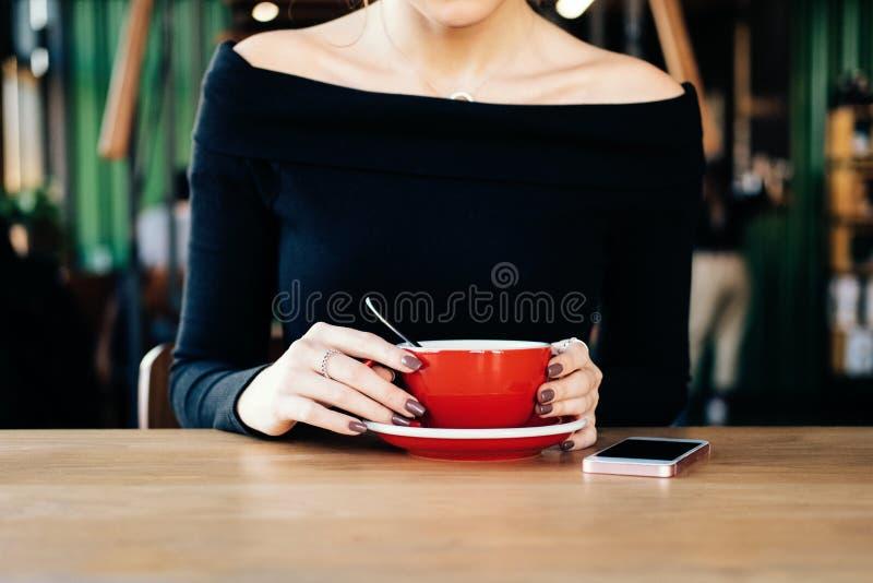 Конец вверх по женским рукам держа красную кружку чая в кафе стоковые изображения