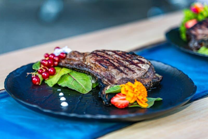 Конец вверх по зажаренному стейку со свежим салатом на черной плите стоковые изображения