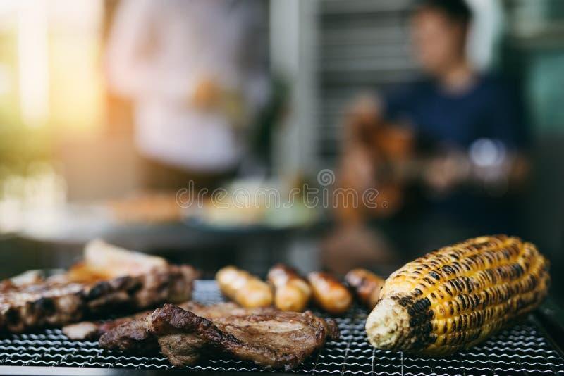 Конец вверх по зажаренным мяс и различной еде на гриле и торжества друзей которые играют гитару и поют совместно в их стоковое фото
