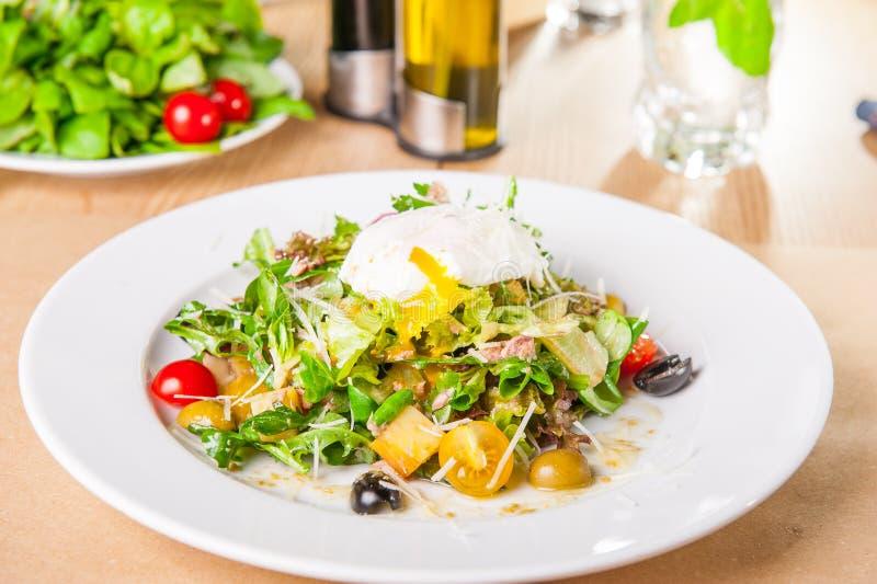 Конец вверх по зеленому салату овоща с тунцом и краденным яйцом на белой плите на деревянной, который служат таблице Селективный  стоковая фотография rf