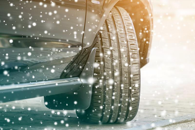 Конец вверх по колесу автомобиля детали с новым черным протектором резиновой автошины на дороге зимы покрытой снегом Концепция тр стоковое фото rf