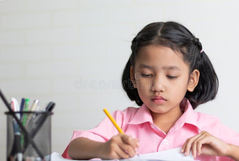 Конец вверх по маленькой девочке делает домашнюю работу умышленно стоковая фотография