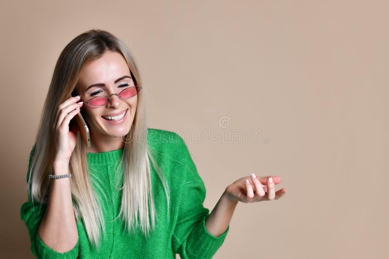 Конец вверх по молодой белокурой женщине говоря с кто-то на ее мобильном телефоне пока смотрящ в расстояние со счастливым выражен стоковое фото rf