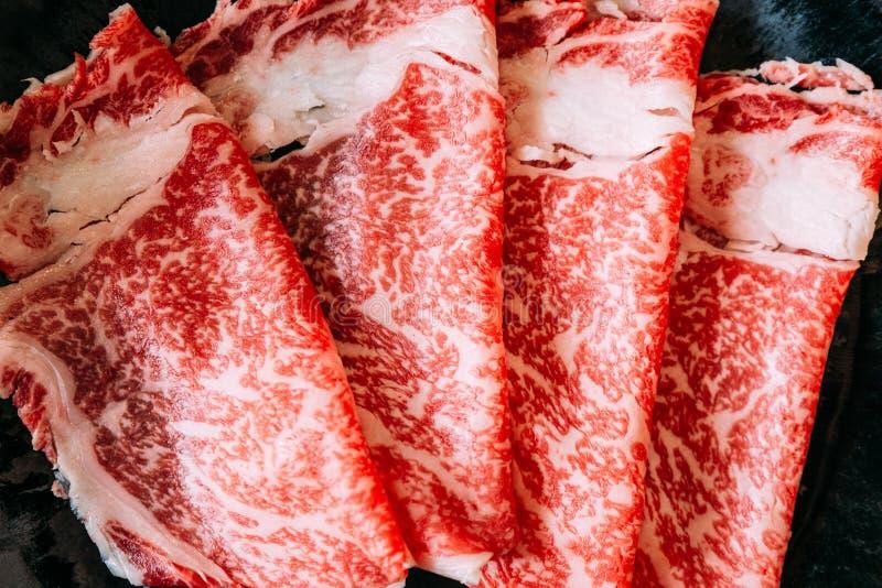 Конец вверх по набору Sukiyaki включая редкую говядину Wagyu A5 кусков с высоко-мраморизованной текстурой в черной плите стоковые фото