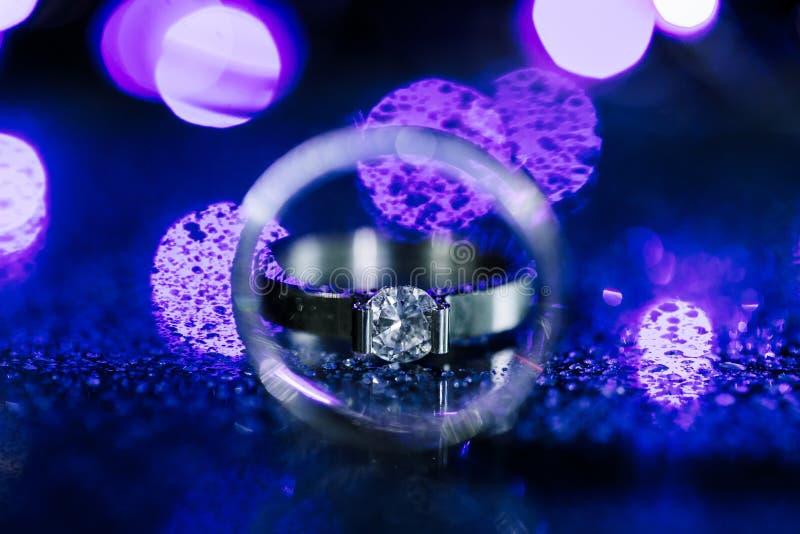 Конец вверх по обручальному кольцу кольца с бриллиантом внутри круга Творческая концепция карты приглашения свадьбы Сверкная пурп стоковая фотография