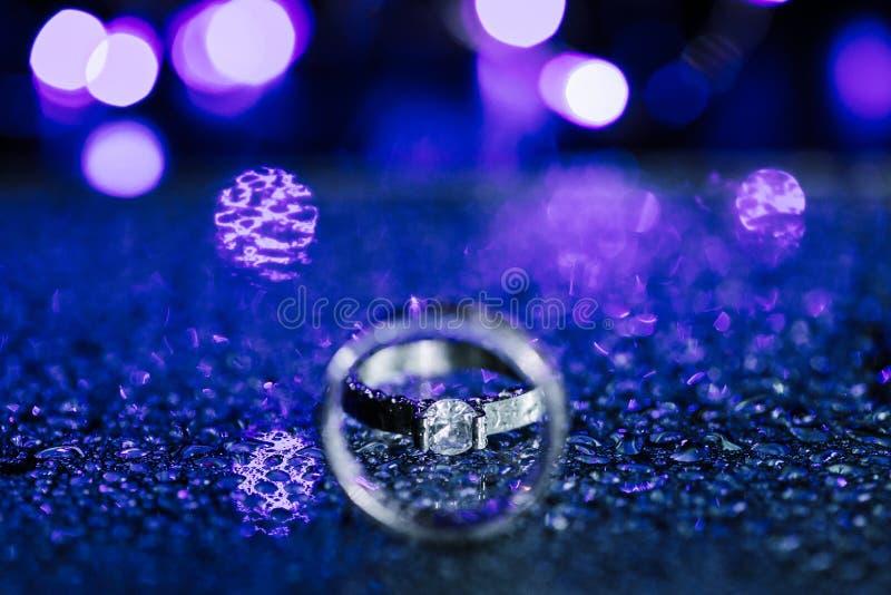 Конец вверх по обручальному кольцу кольца с бриллиантом внутри круга Творческая концепция карты приглашения свадьбы Сверкная пурп стоковые фотографии rf