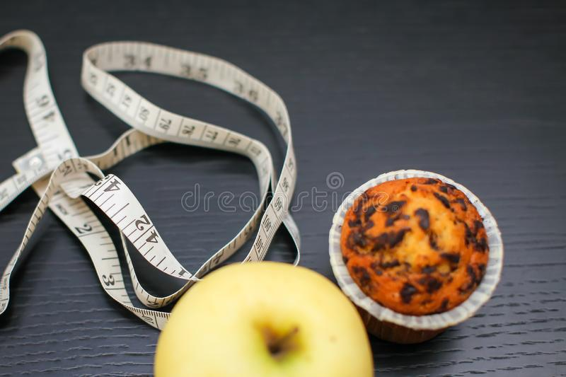 Конец вверх по очень вкусному желтому яблоку с пирожным и измеряя лентой на черном деревянном столе с космосом экземпляра стоковое фото rf