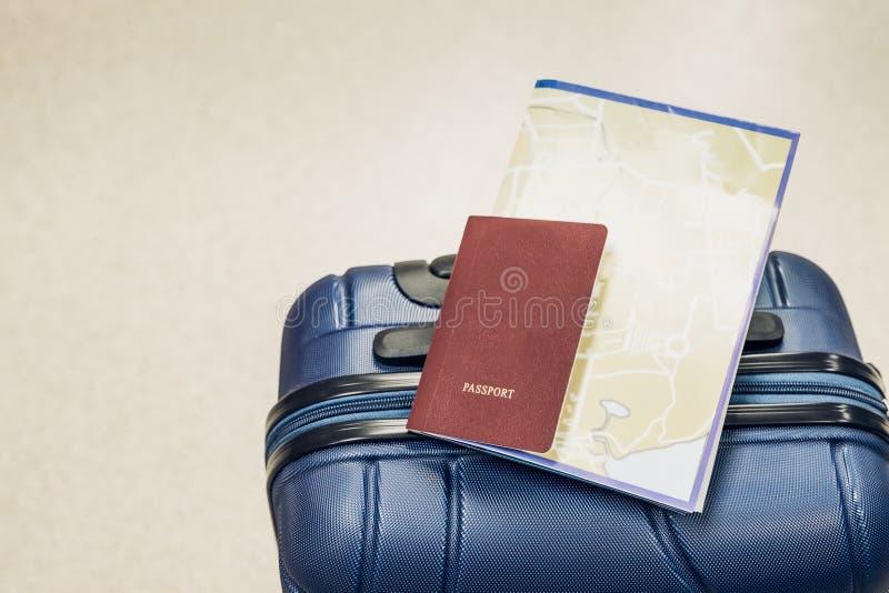 Конец вверх по пасспорту и карта кладут на голубой чемодан на авиапорте, перемещении стоковое фото rf