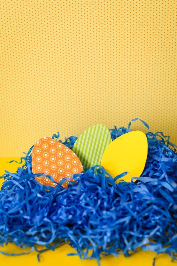 Конец вверх по пасхальным яйцам Handmade бумаги в голубом бумажном гнезде на желтом фоне стоковое изображение
