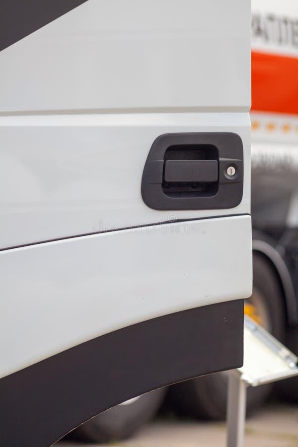 Конец вверх по подрезанному вертикальному фото черной ручки двери на новой яркой белой тележке кабины стоковые изображения