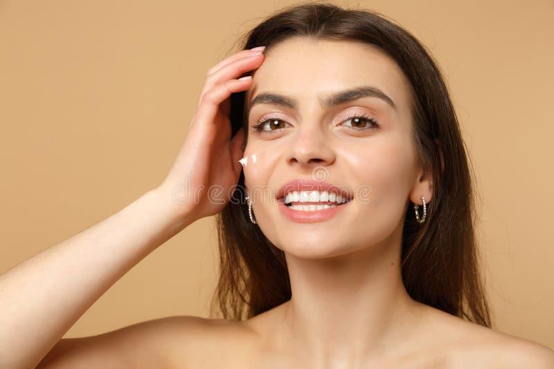Конец вверх по половинной нагой женщине 20s с идеальной обнаженной фигурой кожи составляет приложение лицевой сливк изолированной стоковые изображения rf