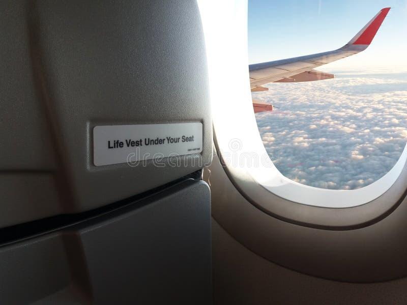"""Конец вверх по предупреждающим словам """"спасательному жилету под вашим местом """"на переднем сидении пассажира и вне крыла воздушных стоковые фотографии rf"""