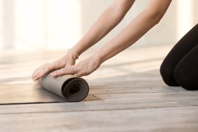 Конец вверх по рукам женщины складывая резиновую циновку йоги стоковые фотографии rf