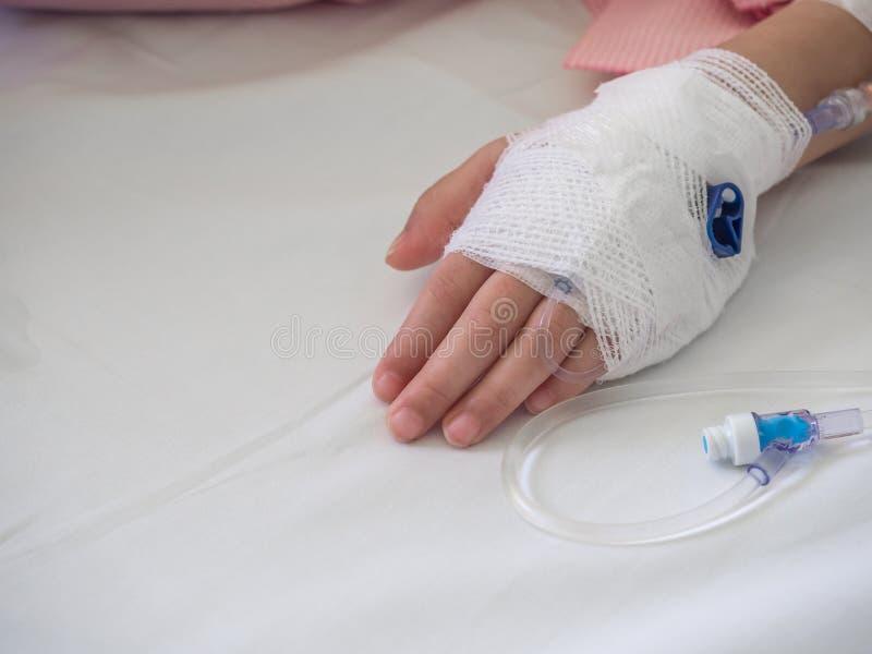 Конец вверх по руке азиатского ребенка с физиологическим раствором стоковые изображения