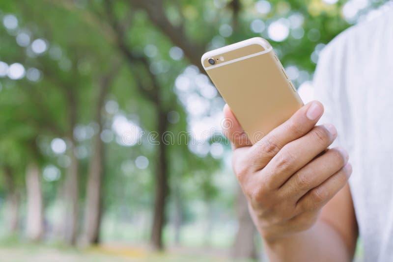 Конец вверх по руке молодого человека использующ на сотовом телефоне во время остатков в парке стоковые фото