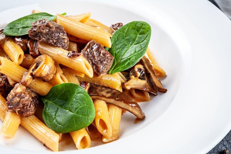 Конец вверх по свежему итальянскому penne макаронных изделий с грибами, базиликом и телятиной Концепция домодельной еды E Обед Tr стоковая фотография rf