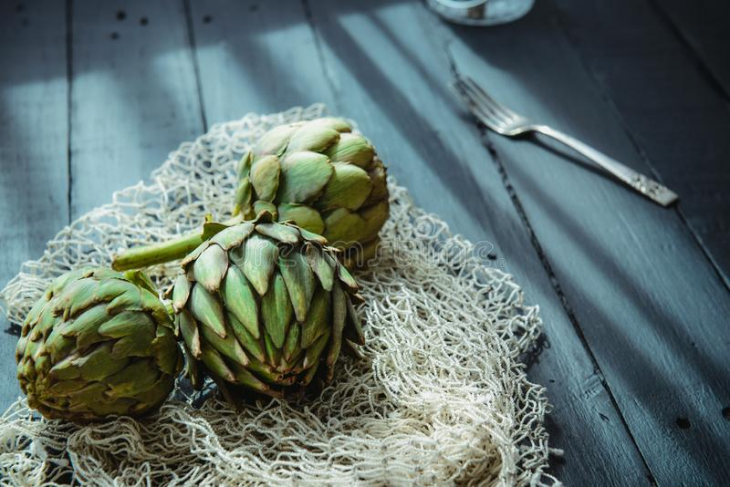 Конец вверх по свежим зеленым артишокам с заплетенным веществом веревочки и кухни на черном деревянном столе назад облегченном ок стоковые фото