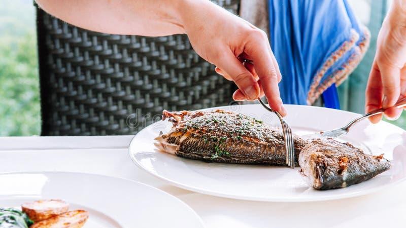 Конец вверх по снятым рукам высекая зажаренные рыб от своих косточек стоковое изображение rf