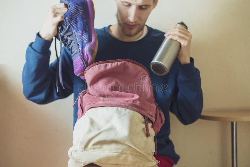 Конец вверх по спортсмену принимая вещи поставок спорта от его сумки перед практикой f стоковая фотография rf