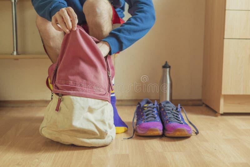Конец вверх по спортсмену принимая вещи поставок спорта от его сумки перед практикой f стоковые изображения rf