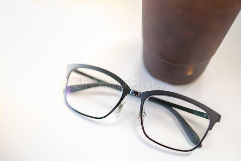 Конец вверх по стеклам oof readding с пластиковой чашкой замороженного черного кофе на белой таблице стоковое фото rf
