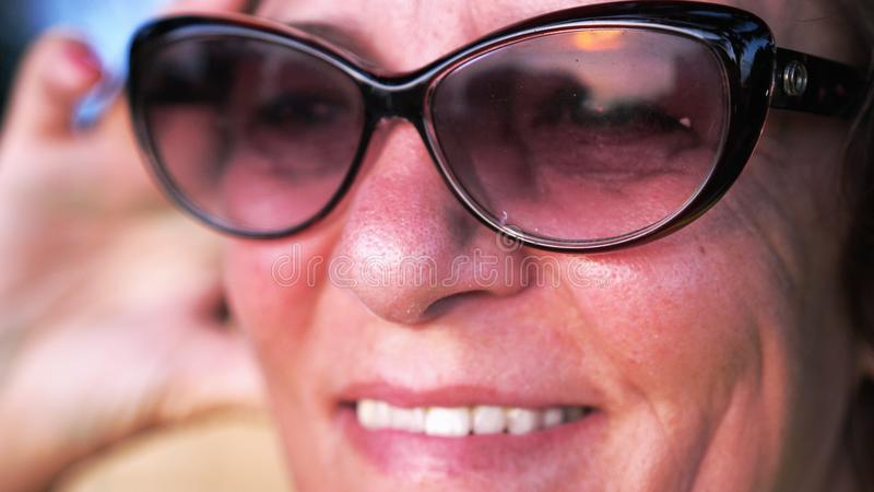 Конец вверх по съемке зрелой женщины улыбок в постаретых нося солнечных очках смотрит заход солнца стоковые фотографии rf