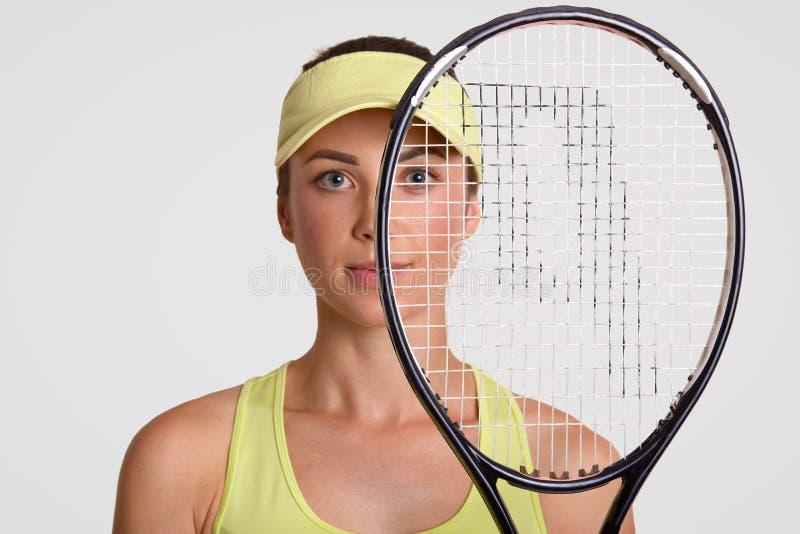 Конец вверх по съемке приятной смотря здоровой женщины держит ракетку тенниса, был бегуном вверх, взгляды через сеть, носит крышк стоковые фотографии rf