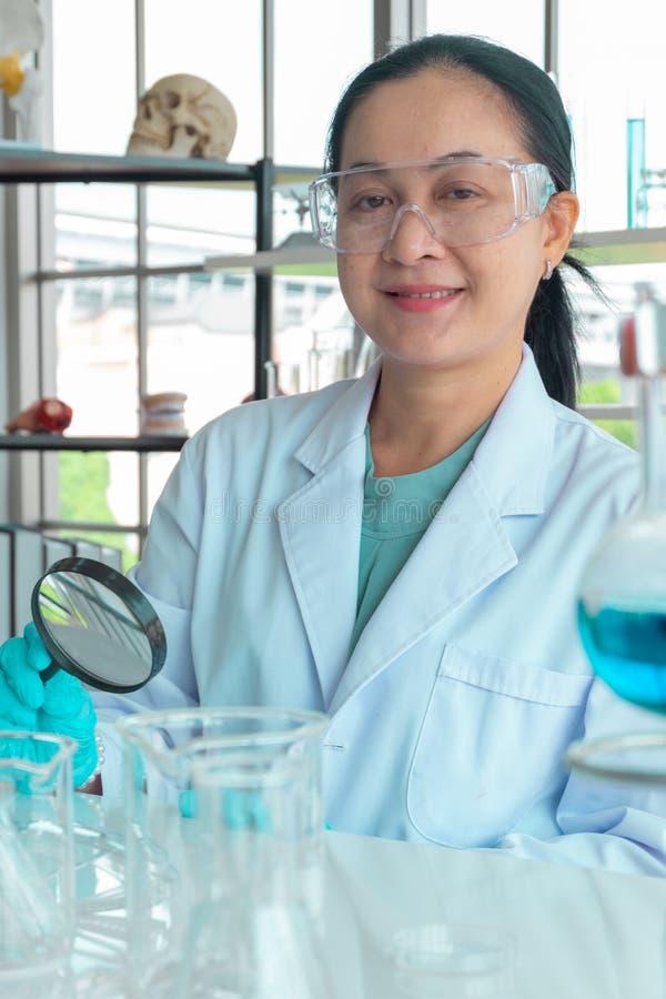 Конец вверх по съемке, ученым среднего возраста азиатским женским, нося стеклам и руке держа лупу стоковая фотография rf