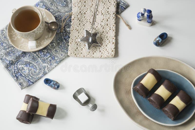 Конец вверх по типичному голландскому печенью торта с марципаном и шоколадом, вызвал mergpijpje Белая таблица, чашка чаю стоковые изображения rf