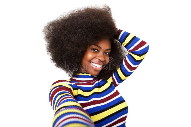 Конец вверх по усмехаясь молодой чернокожей женщине принимая selfie против изолированной белой предпосылки стоковое фото