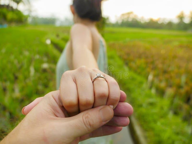 Конец вверх по человеку рук пар держа счастливую руку жениха с обручальным кольцом диаманта на ее пальце после предложения свадьб стоковые изображения