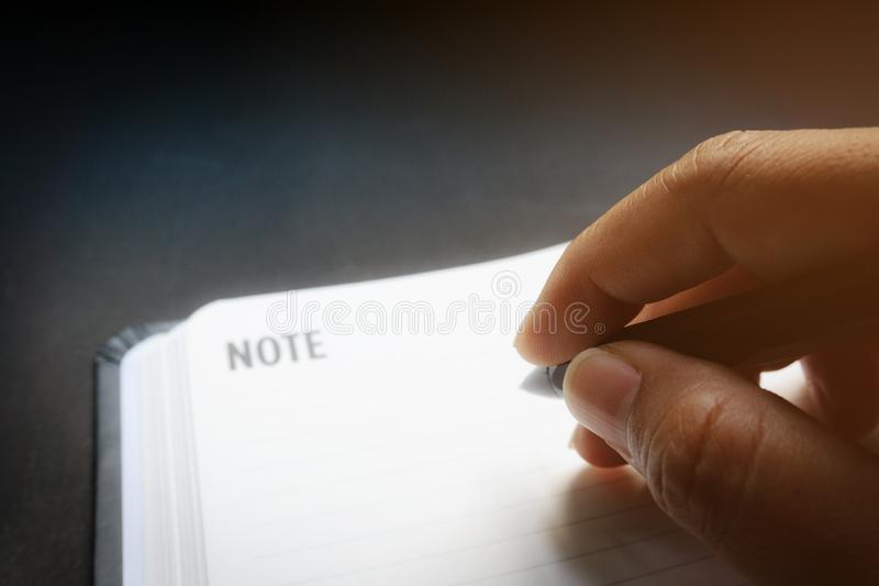 Конец вверх по человеческим рукам с черной ручкой писать что-то на тетради незаполненной с черной предпосылкой стола в драматичес стоковое изображение rf