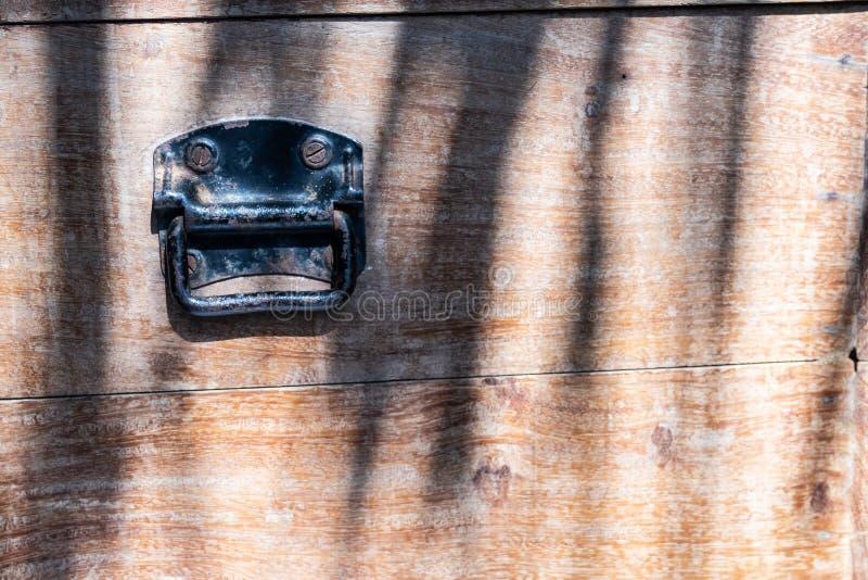 Конец вверх по черной ржавой винтажной ручке металла на предпосылке деревянной коробки стоковое изображение