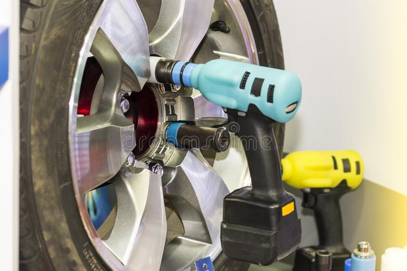 Конец вверх по электрическому инструменту ключа для собрания или ООН устанавливают колесо автомобиля на гараж или мастерскую стоковые фото