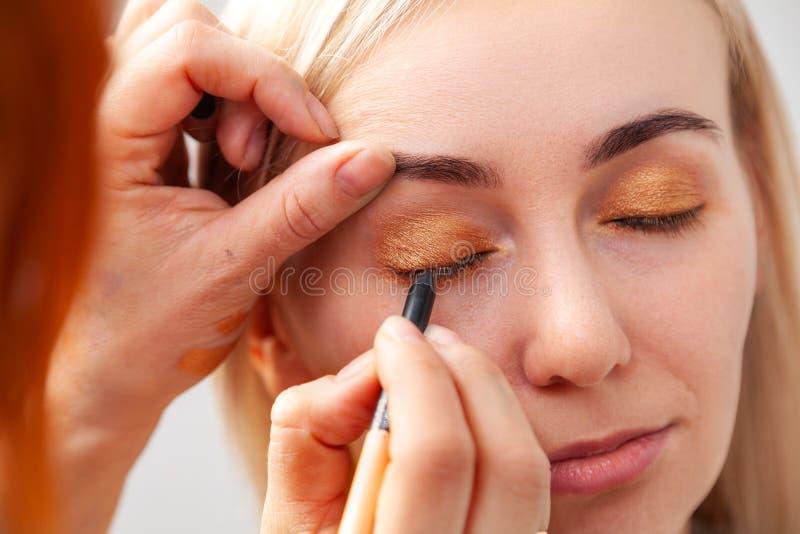 Конец-вверх приложения макияжа в салоне на модели в восточном стиле, художник макияжа наводит золотые коричневые тени и стоковые фотографии rf