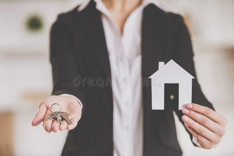 конец вверх Риэлтор держа ключи и модель дома стоковая фотография rf