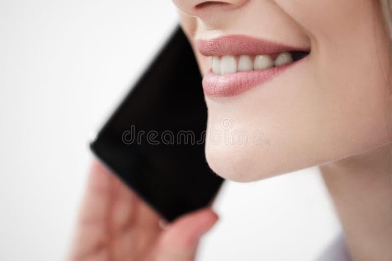 Конец-вверх рта и губ женщины говоря на смартфоне на белой предпосылке стоковые изображения rf