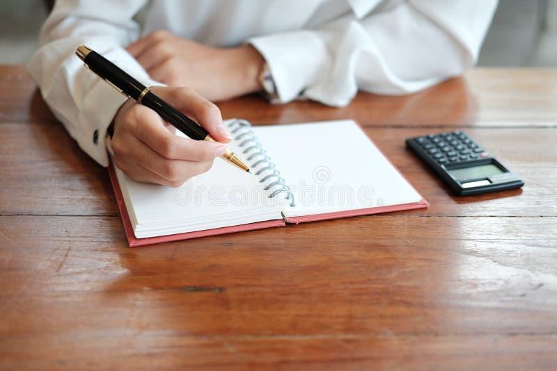 конец вверх рука молодой ручки удерживания женщины студента для писать дальше стоковые фото