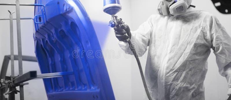 Конец-вверх, рука элементов тела автомобиля картины ремонтника в камере краски стоковое изображение rf