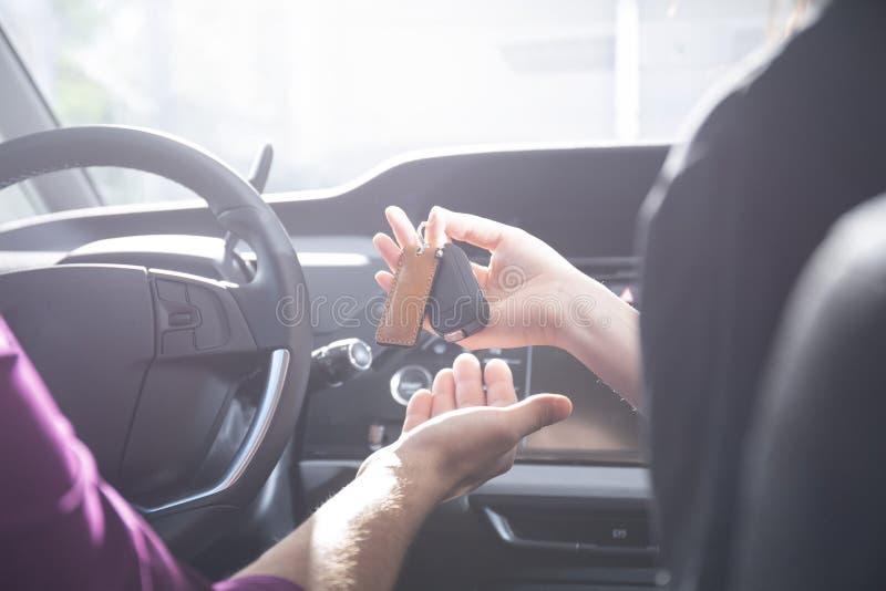 Конец-вверх руки давая ключи автомобиля к водителю внутри автомобиля стоковые фотографии rf