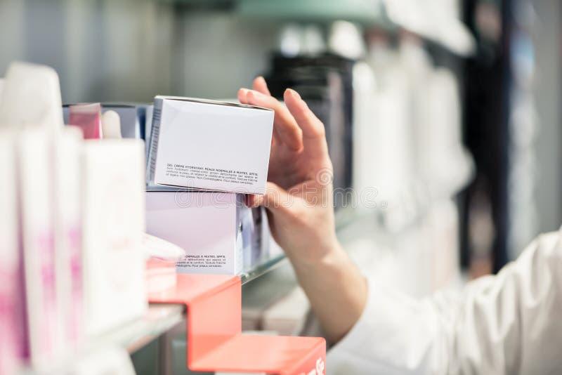 Конец-вверх руки женского аптекаря выбирая вверх самый лучший продукт стоковые фото