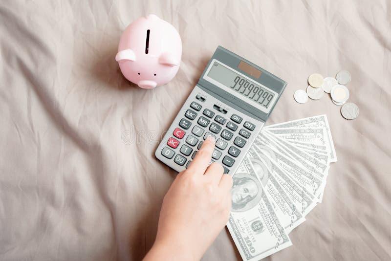 Конец-Вверх руки женщины использует калькулятор для высчитанных учитывая сбережений денег или заявки на ее спальне, дела расхода стоковая фотография