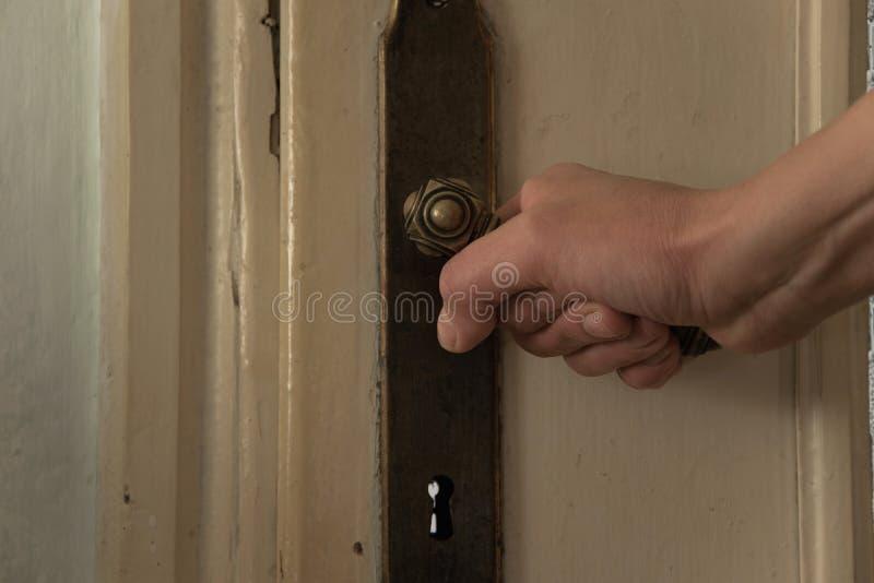 Конец вверх руки женщины раскрывает старую дверь стоковые фото